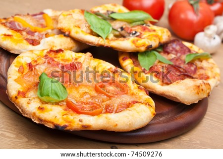 different kinds of small pizza on a cutting board and ingredients - stock photo