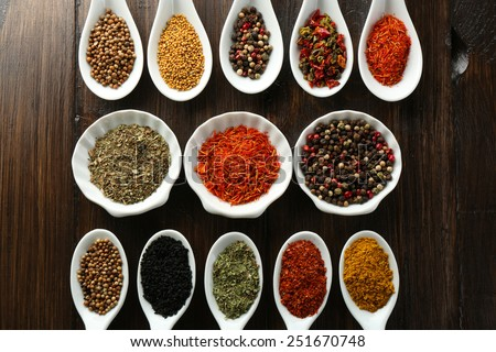 Different kinds of spices in bowls and spoons, close-up, on wooden background