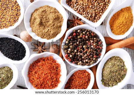 Different kinds of spices in ceramics spoons, close-up, on wooden background