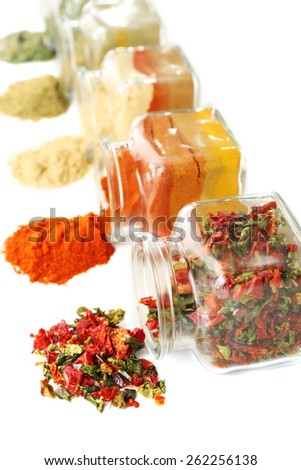Different kinds of spices in glass bottles isolated on white - stock photo