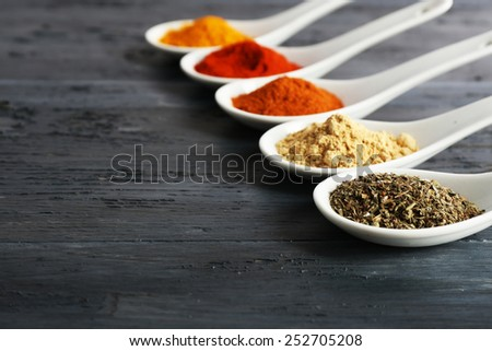 Different kinds of spices in spoons on wooden background - stock photo