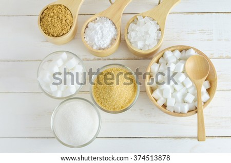 Different kinds of sugar in glass and wooden bowl on white wooden table - brown, white, crystal, cube and Icing sugar