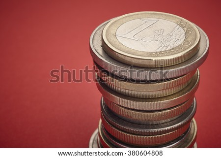 Different kinds on coins over a red background. Macro detail. Horizontal
