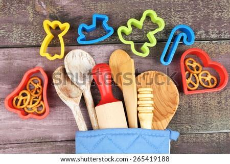 Different kitchen utensils in potholder on wooden background - stock photo