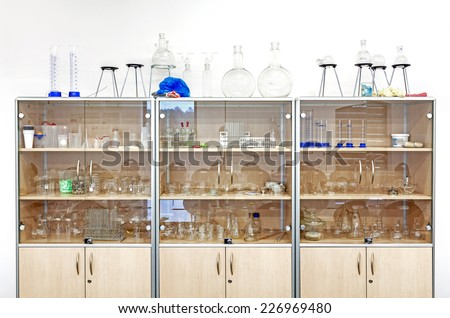 Different laboratory glassware and equipment on shelves. - stock photo