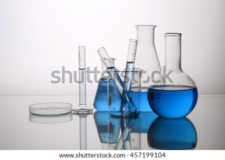 Different laboratory glassware with color liquid and with reflection
