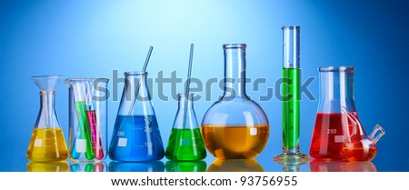 Different laboratory glassware with color liquid and with reflection on blue background - stock photo