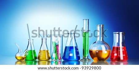Different laboratory glassware with color liquid and with reflection on blue background
