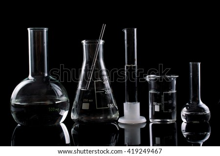 Different laboratory glassware with water to a reflection on a black background