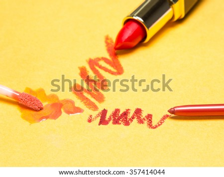 Different lip makeup cosmetics: lip liner, lip gloss and lipstick orange color on yellow background. Focus on lip liner