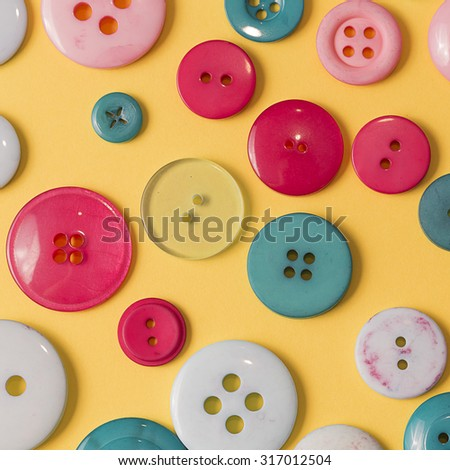 Different many green red and white sewing buttons on a yellow background close up still - stock photo
