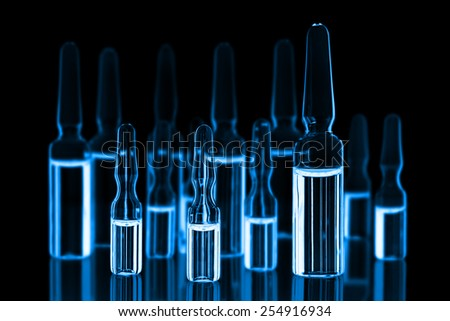 Different medical ampules toned blue on black background - stock photo