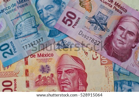 Different Mexican money bills stacked over each other forming a money background.