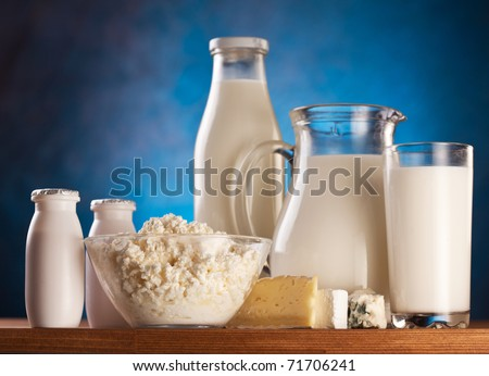 Different milk products: cottage cheese, cream, milk.  On a blue background.