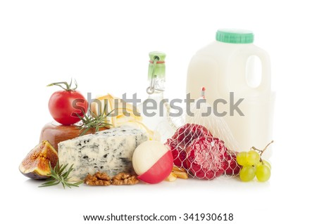 Different milk products. Milk in container, smoked cheese, blue cheese, babybel cheese with walnuts, herbs, tomato, grapes and fig on white background - stock photo