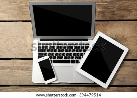 Different modern devices on wooden table - stock photo