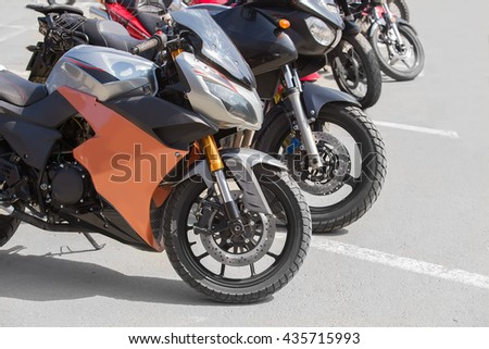 different motorcycles on parking on asphalt  closeup