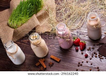 Different natural milkshakes on the background of hay and sackcloth.  - stock photo