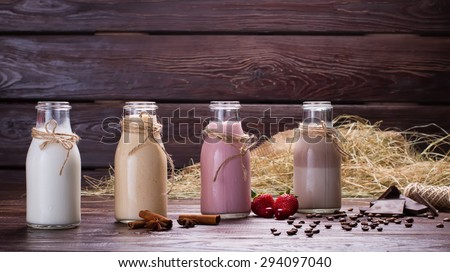 Different natural milkshakes on the background of hay and sackcloth. Beautiful interer. - stock photo