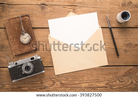 Different objects and envelope on a wooden table   - stock photo