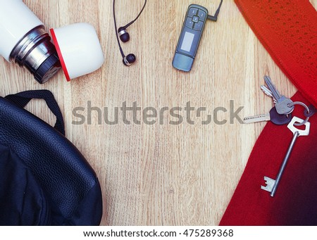 Different objects on wooden background: backpack, thermos, earphones, music player, keys, scarf