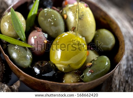 different olive fruits on wooden trunk of an olive tree - stock photo