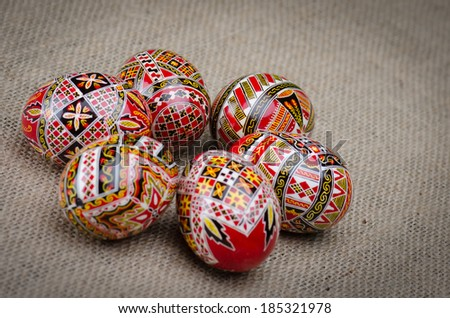 Different painted easter eggs with geometric motifs on hemp canvas