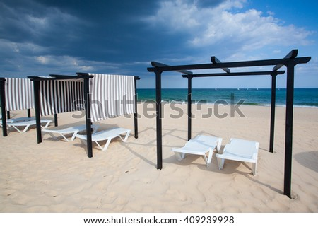 Different parasols and sun loungers on the empty beach on Tavira island before storm,Algarve. Portugal - stock photo