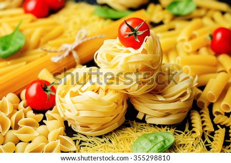 different pasta with tomatoes and spinach on a black background. toning. selective Focus - stock photo