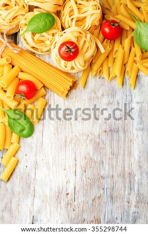 different pasta with tomatoes and spinach on a white wood background. toning. selective Focus - stock photo