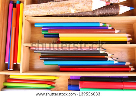 Different pencils in wooden crate, close up