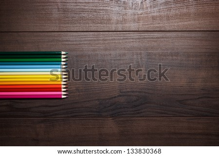 different pencils on the brown wooden table background - stock photo