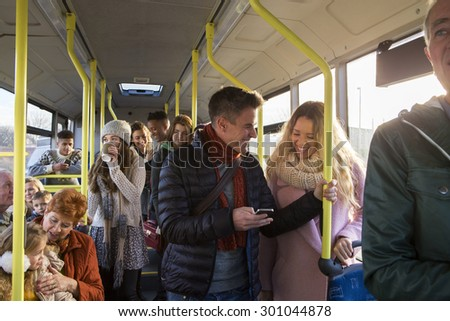 Different people can be seen travelling on the bus. Some are talking to other people, others are using technology or looking out the window.   - stock photo