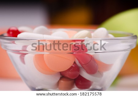 Different pills in a bowl on white surface against green  and orange background  - stock photo