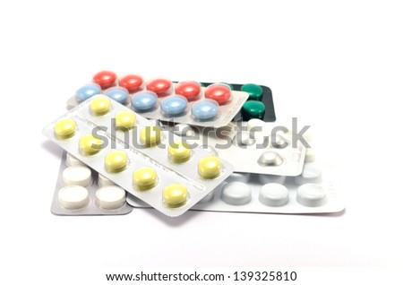 different pills on plate with against white background