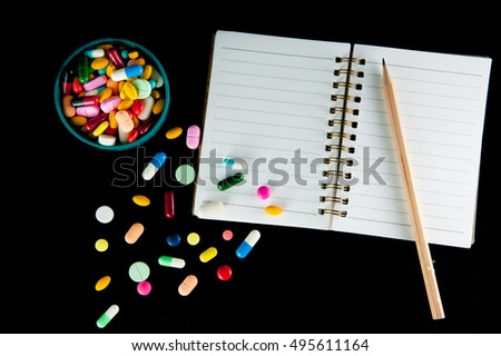 Different pills with notebook and pencil on black background
