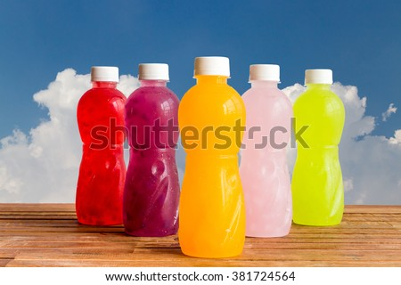 different Plastic Bottle of juice beverage on blue background - stock photo