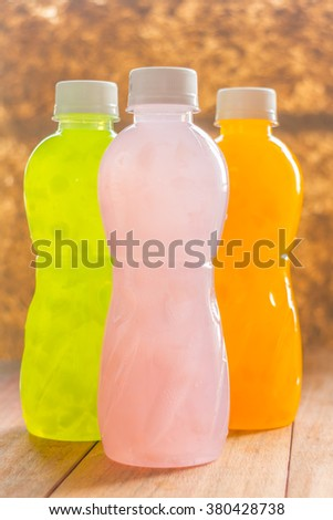 different Plastic Bottle of juice beverage on wooden table - stock photo