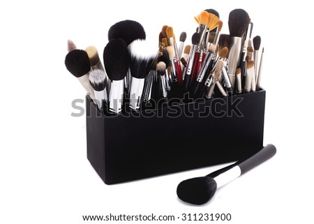 Different professional natural soft make-up brushes for eyeshadow powder and facial foundation for visagistes black and brown colors in plastic box on white background, horizontal picture - stock photo
