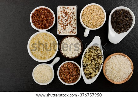 Different rice in bowls on black background - stock photo