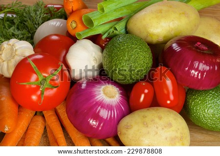 Different ripe vegetables lying on a wooden table as a background - stock photo