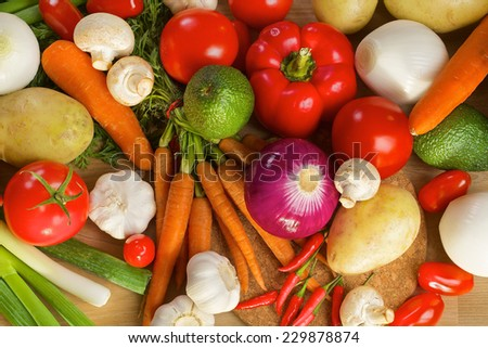 Different ripe vegetables lying on a wooden table as a background