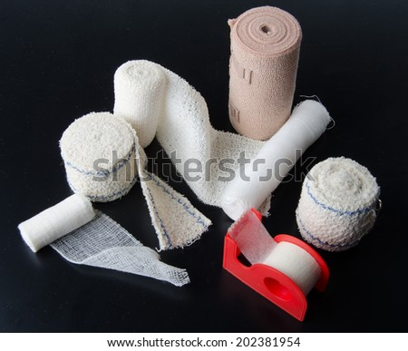 Different rolls of medical bandages and sticking plaster on a black background - stock photo