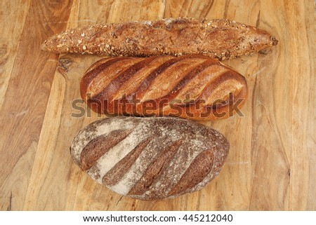 different rye and white flour bread loaf with french fresh baguette on light wooden table background - stock photo