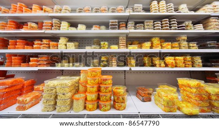 Different salads in plastic containers on shelves in large store - stock photo