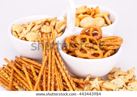 Different salted crackers in bowl on white background.