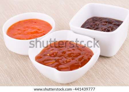 Different sauces in saucers on beige cloth background.