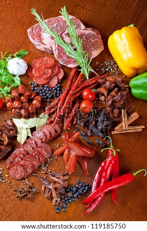 different sausage and meat on a celebratory table with spices and vegetables