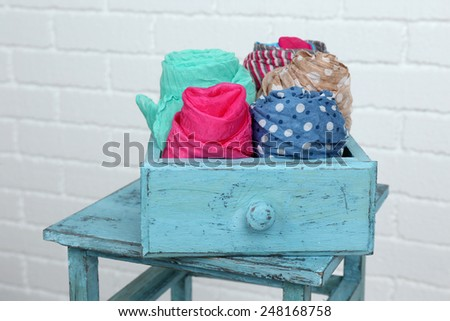 Different scarves in color drawer on white brick wall background - stock photo