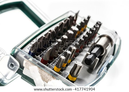 Different Security screwdriver drill heads and accessories in a box. Set of screwdriver metal bits set over white isolated background, different foreshortenings. - stock photo